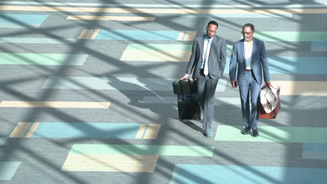 business travelers walking through airport - flugpassagier stock-videos und b-roll-filmmaterial