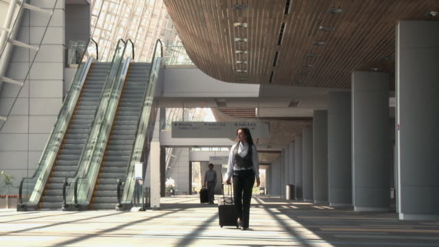 Business travelers walking through airport with bags