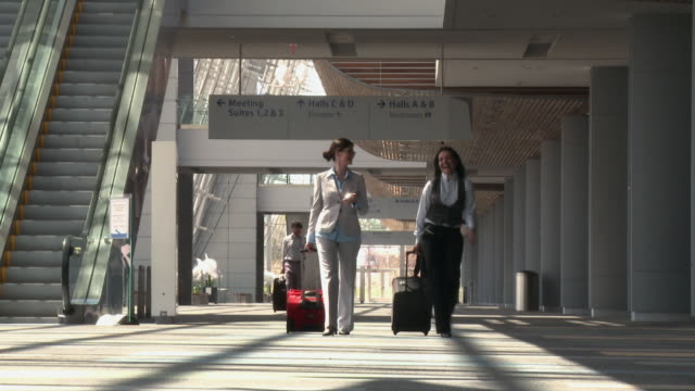 business travelers walking through airport with bags - reisegepäck stock-videos und b-roll-filmmaterial