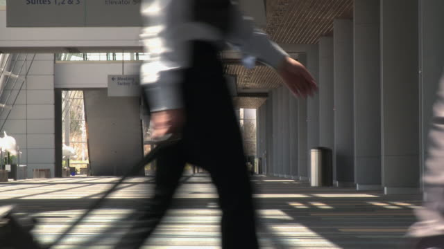business travelers walking through airport with bags - rolltreppe stock-videos und b-roll-filmmaterial