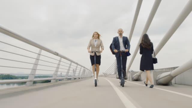 stockvideo's en b-roll-footage met slo mo bedrijfsvrouw en mens die elektrische scooters berijden aan het werk - mid volwassen mannen