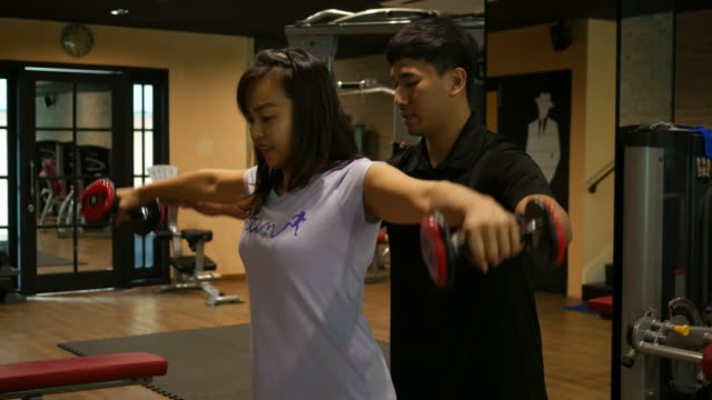 Business woman and personal trainer in gym