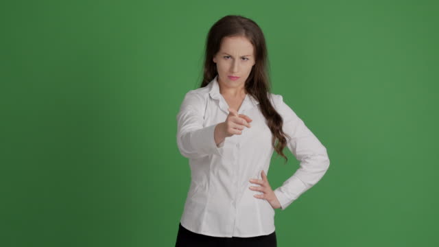 business woman angrily looks and threatens with finger on green background - blouse stock videos & royalty-free footage