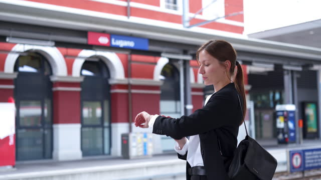 business woman checking her watch while waiting for a train at a station - checking the time stock videos & royalty-free footage