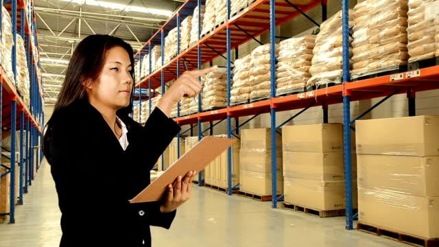 ビジネスの女性の倉庫在庫確認 - 商品点の映像素材/bロール