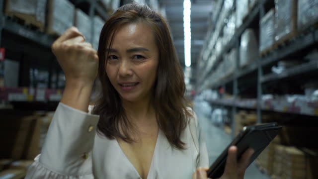 business woman checking inventory on digital tablet , pride gesturing