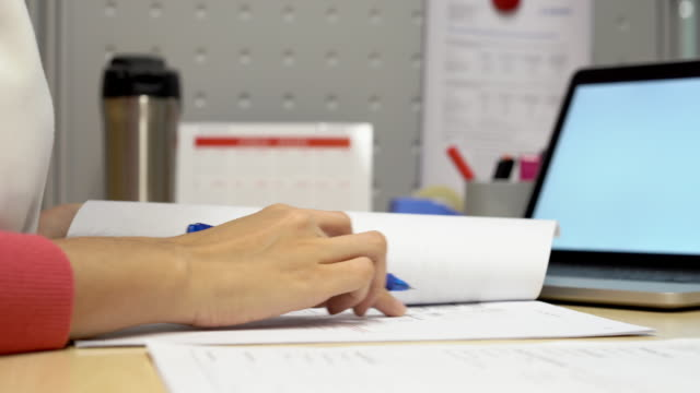 Business woman checking with sign on paper document report at office.
