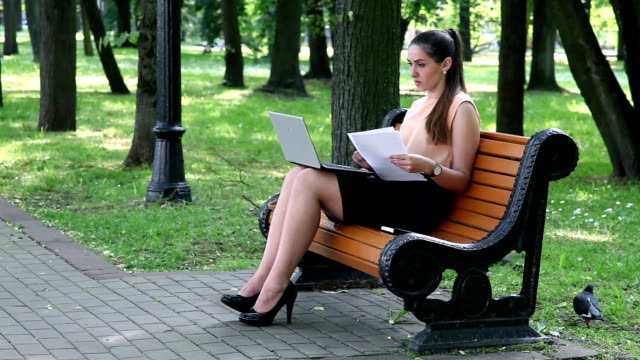 Business woman comparing data from laptop screen with printed document