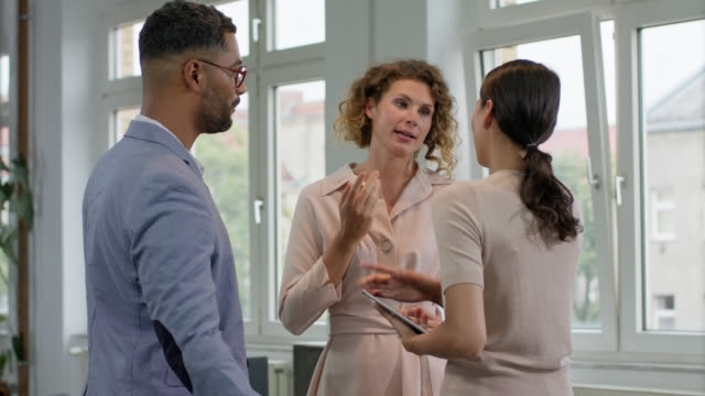 business woman discussing together with two colleagues in good working atmosphere. - male with group of females stock videos & royalty-free footage