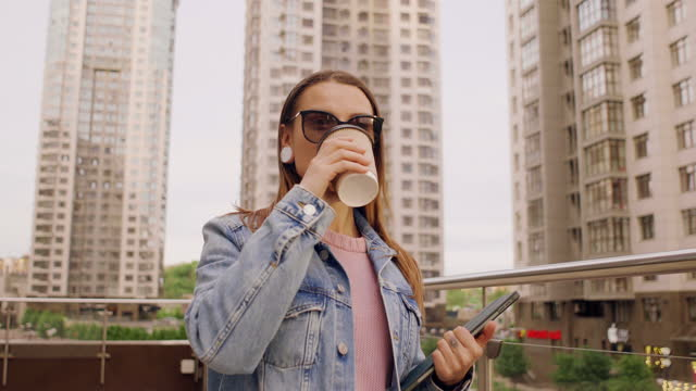 vidéos et rushes de business woman drinking coffee holding tablet in hand walking around the city - 25 29 years