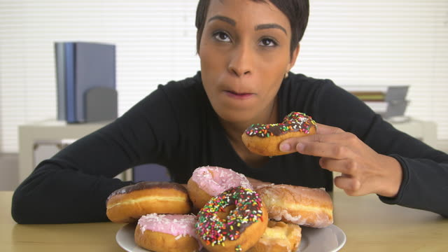 business woman eating a pile of donuts - donut stock videos and b-roll footage