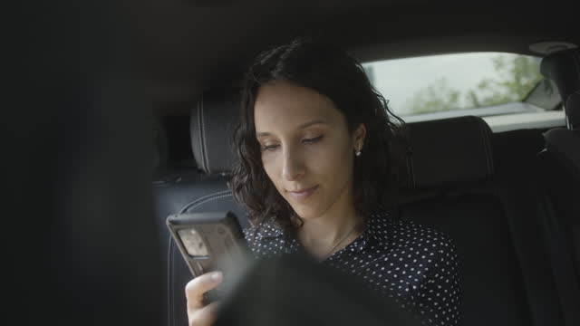 business woman executive sitting in car with driver using smart phone - passenger seat stock videos & royalty-free footage