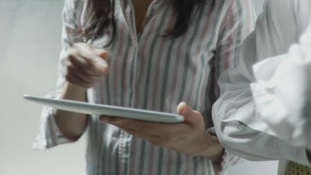 CU TU Business woman explaining business to business man using digital tablet / Brooklyn, New York, USA
