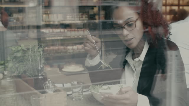 Business woman going through messages on smartphone during lunch break