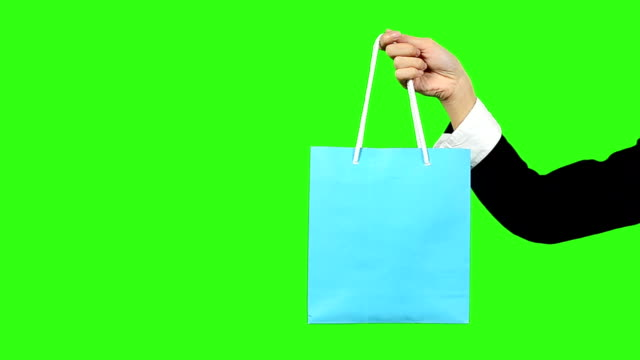 stockvideo's en b-roll-footage met business woman hand holding shopping bag with green screen background - keyable