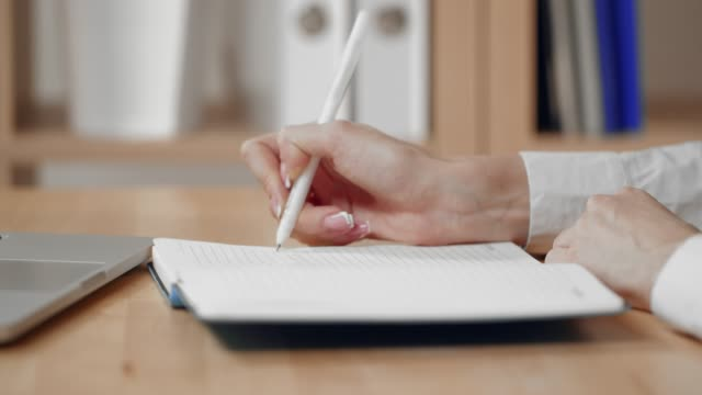 business woman hand is writing on a notepad with a pen and using a laptop computer. - note pad stock videos & royalty-free footage