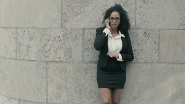 vídeos de stock e filmes b-roll de business woman having conversation on smart phone outside of office building - saia