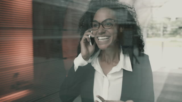 Business woman having pleasant conversation on mobile phone