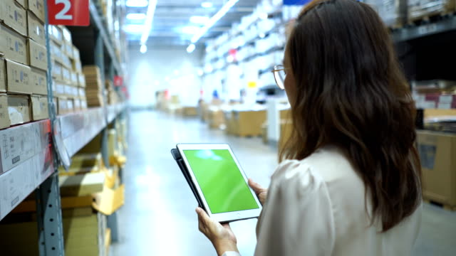 business woman in a warehouse store checking inventory on digital tablet green screen , chroma key - touchpad stock videos & royalty-free footage