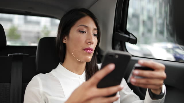 business woman in car using facial recognition technology to unlock smart phone and make payment - identität stock-videos und b-roll-filmmaterial