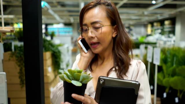 donna d'affari in negozio di fiori controllare l'inventario su tablet digitale e utilizzando il telefono - organizzatore elettronico video stock e b–roll