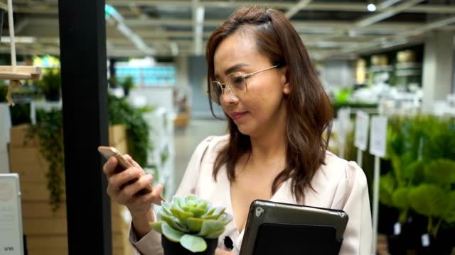 vidéos et rushes de femme d'affaires dans le magasin de fleurs recherche inventaire sur tablette numérique et l'utilisation de téléphone - satisfaction