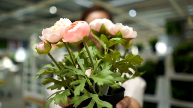 business woman in flower shop giving bouquet of pink roses