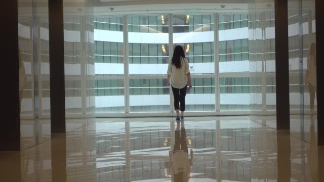 business woman in office building - einsamkeit stock-videos und b-roll-filmmaterial