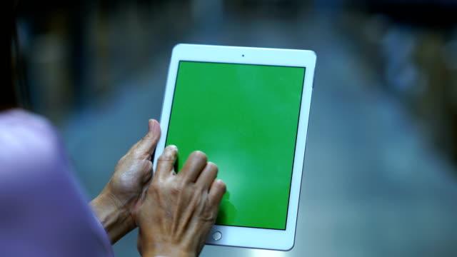 ビジネス ・ ウーマンはクロマキー デジタル タブレット緑画面で、チェックのインベントリを保存します。 - メガストア点の映像素材/bロール