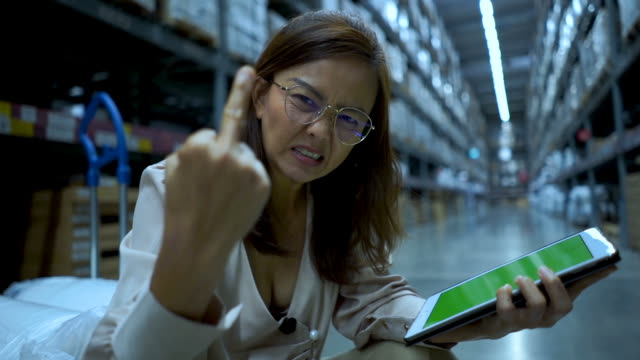 business woman in store checking inventory on digital tablet  ,serious emotion ,showing middle finger - business plan stock videos & royalty-free footage
