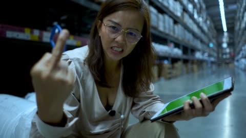 stockvideo's en b-roll-footage met zakenvrouw in winkelvoorraad controle op digitale tablet, ernstige emotie, middelvinger weergegeven: - merchandise