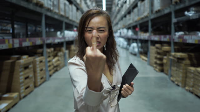 business woman in store checking inventory on digital tablet ,serious emotion ,showing middle finger - warehouse stock videos & royalty-free footage