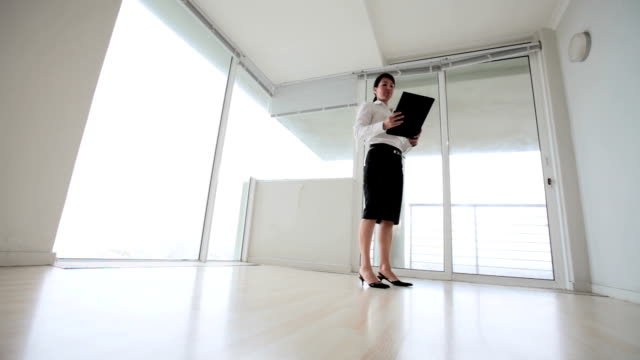 business woman inspects empty apartment office - downsizing stock videos & royalty-free footage