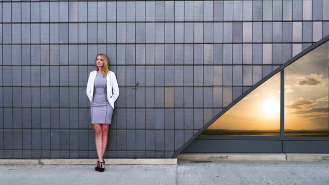 business woman leans up against building, reflection of sun in window - corporate business stock videos & royalty-free footage