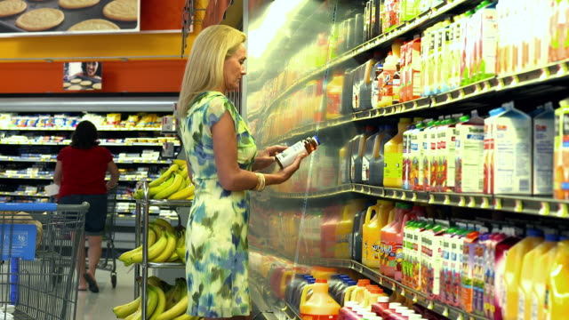MS Business woman looking at nutritional information on  juice bottle in food supermarket / La Quinta, California, United States