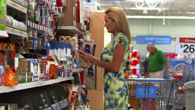 MS Business woman looking  at products in paint supply section of big box store   / La Quinta, California, United States