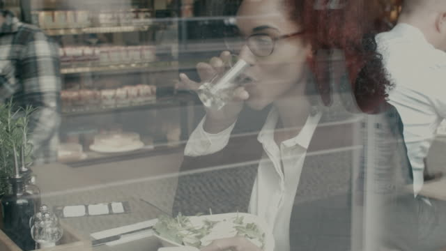 business woman looking at smart phone thinking, drinking water during lunch break - only mid adult women stock videos & royalty-free footage