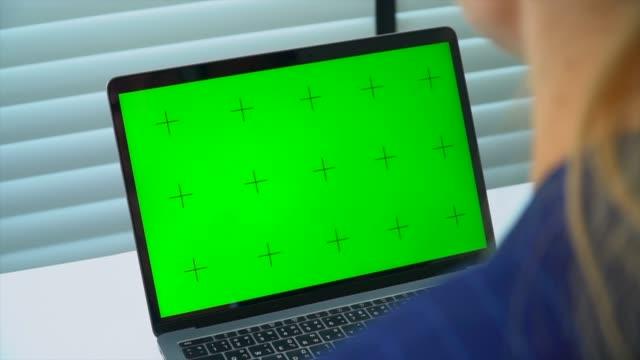 geschäftsfrau schaut computer grünen bildschirm - über die schulter stock-videos und b-roll-filmmaterial