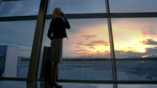 business woman observing the sunset through the glass wall at the airport, taking a phone call and walking away - gate stock videos & royalty-free footage