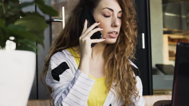vidéos et rushes de femme d'affaires sur le téléphone devant l'ordinateur portatif. - devant