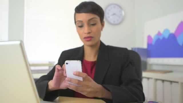 vidéos et rushes de business woman picking up cell phone while working - rouge à lèvres rouge