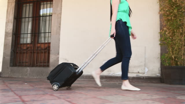 business woman pulling a suitcase - wheeled luggage stock videos and b-roll footage