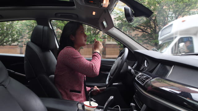 Business woman putting on makeup in her car, prior to entering workplace.