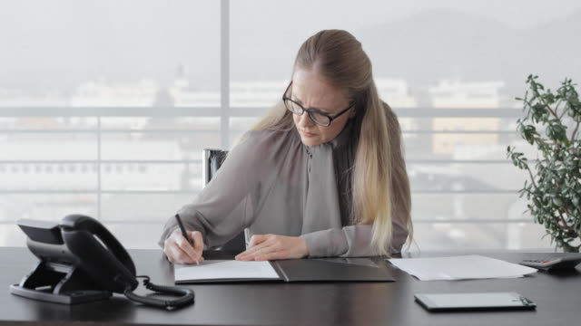 DS Business woman reading a document and signing a paper