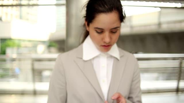 vídeos y material grabado en eventos de stock de mujer de negocios relajante en smartphone después del trabajo - sólo mujeres jóvenes
