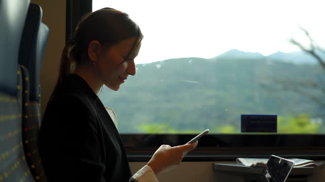 business woman riding on a train near a lake checking her phone - making money stock videos & royalty-free footage