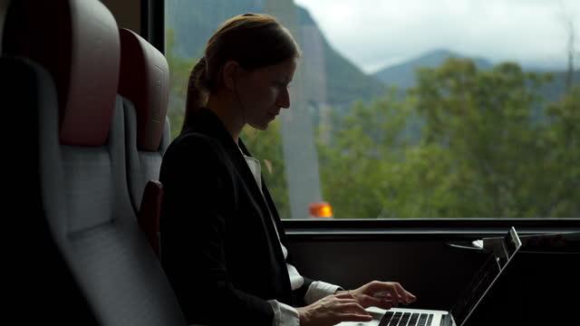 vidéos et rushes de femme d'affaires conduisant sur un train près d'un lac utilisant un ordinateur portatif - voyage d'affaires