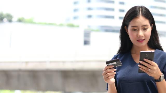 スマート フォンでオンライン ショッピング ビジネスの女性 - 金銭に関係ある物点の映像素材/bロール