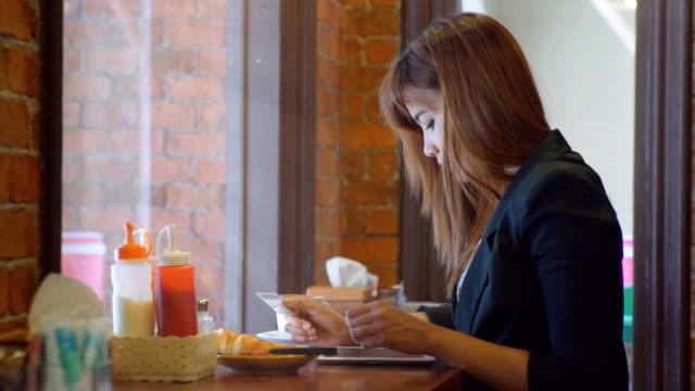 Donna d'affari, lo lo shopping online con compressa PC al ristorante