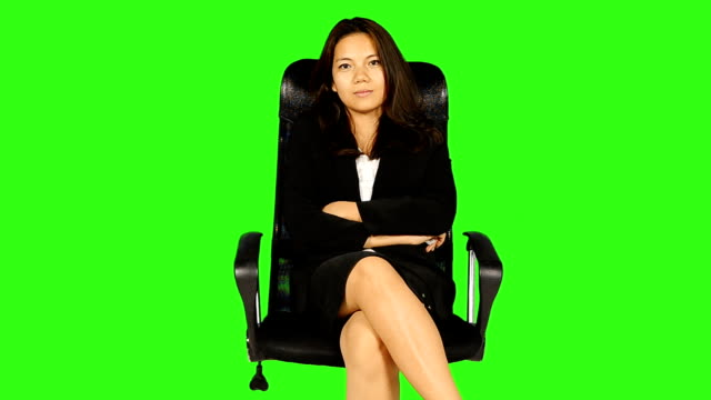 business woman sitting on a chair with green screen background - matte board stock videos & royalty-free footage